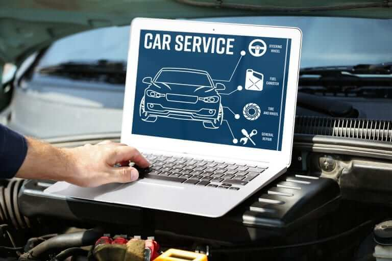A Mechanic looking at a car service on his laptop