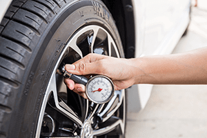 A person checking a tyre's pressure