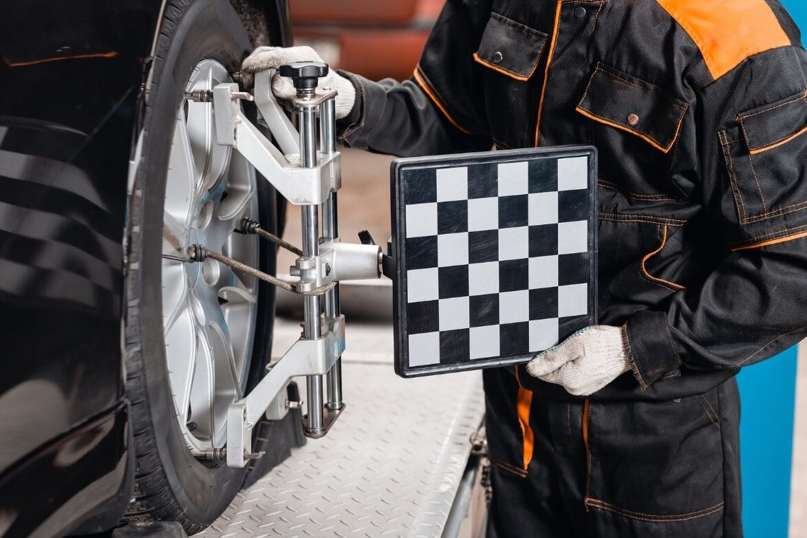 A mechanic working on a wheel alignment
