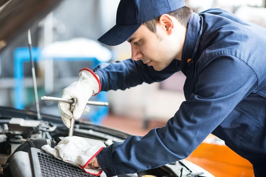 A mechanic working on a car under the bonnet